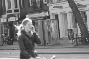 A woman cycling while using a smartphone in Amsterdam