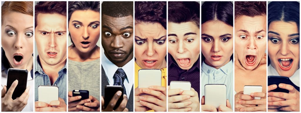 shocked group of people looking at smartphones
