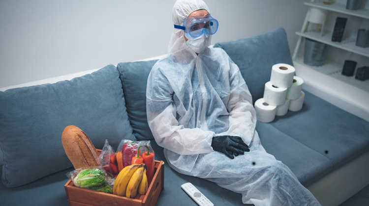 woman on sofa in full PPE